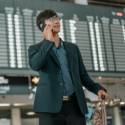 Asian man with suitcase using cellphone at airport