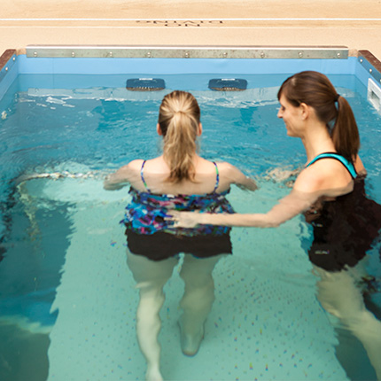 Woman and therapist inside small pool for aquatherapy