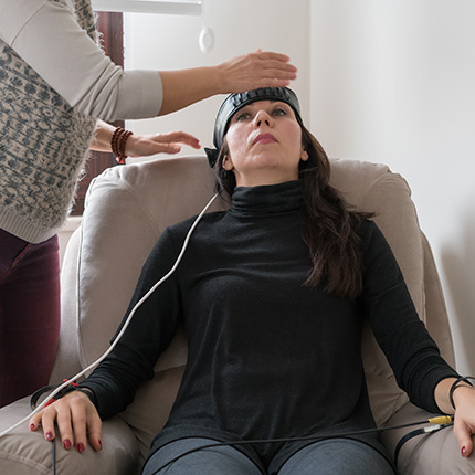 Therapist applying electrical sensors to woman sitting on couch