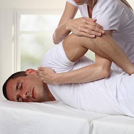 Woman chiropractor applying pressure on man's shoulder