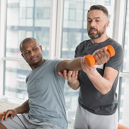 African-american being assisted by therapist during shoulder exercises