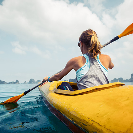 Blonde woman kayaking on cloudy day