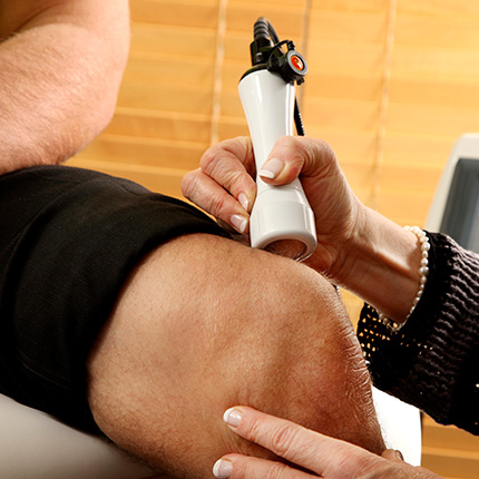 Therapist applying laser on male knee