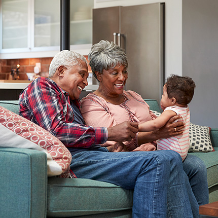 Senior african-american couple playing with grandchild on couch