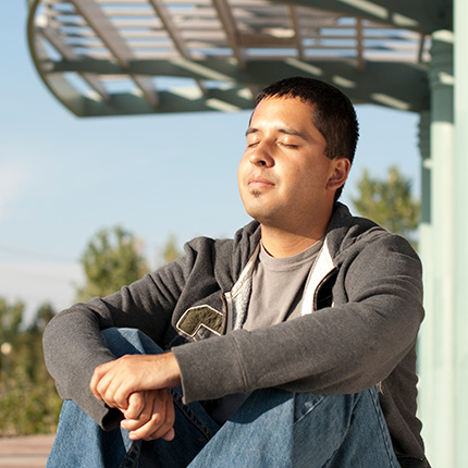 Young man meditating, sitting on the floor, wearing casual clothes