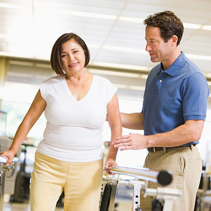 Middle-aged woman being assisted by therapist during walking rehabilitation