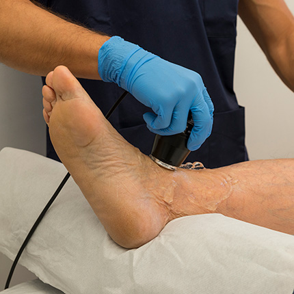 Doctor with gloves applying ultrasound to ankle