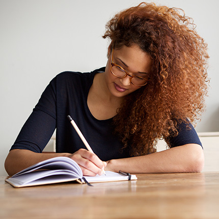 Woman hand writing on notebook